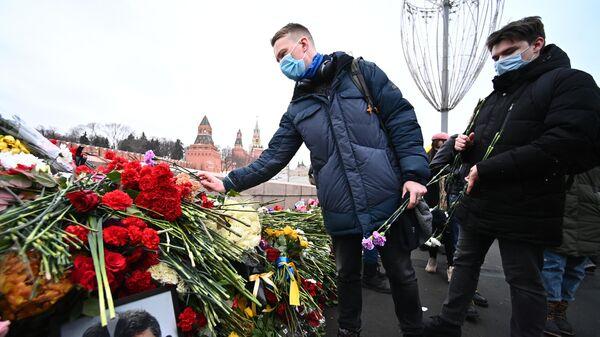 Молодые люди возлагают цветы на месте гибели политика Бориса Немцова на Большом Москворецком мосту в Москве