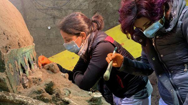 Археологи во время раскопок большой четырехколесной церемониальной колесницы, обнаруженной на месте древнеримского города Помпеи