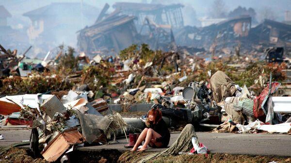Женщина сидит на дороге в разрушенном городе Натори, префектура Мияги, после мощного землетрясения и цунами на севере Японии. 13 марта 2011 года