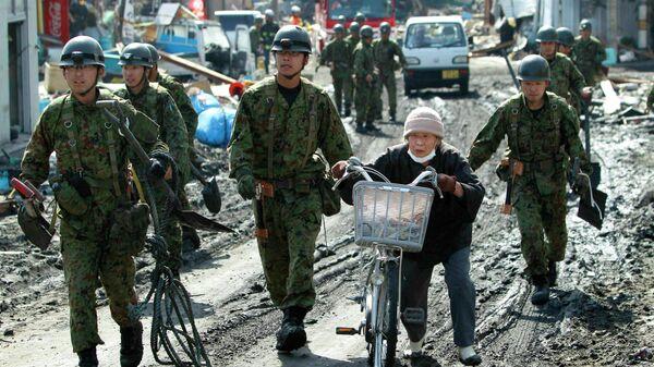 Солдаты Сухопутных сил самообороны Японии призывают пожилую женщину перебраться на возвышенность во время предупреждения о цунами в гавани города Сома, префектура Фукусима, Япония. 14 марта 2011 года