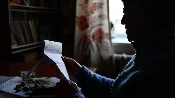 Пенсионерка держит в руках квитанцию ЖКХ