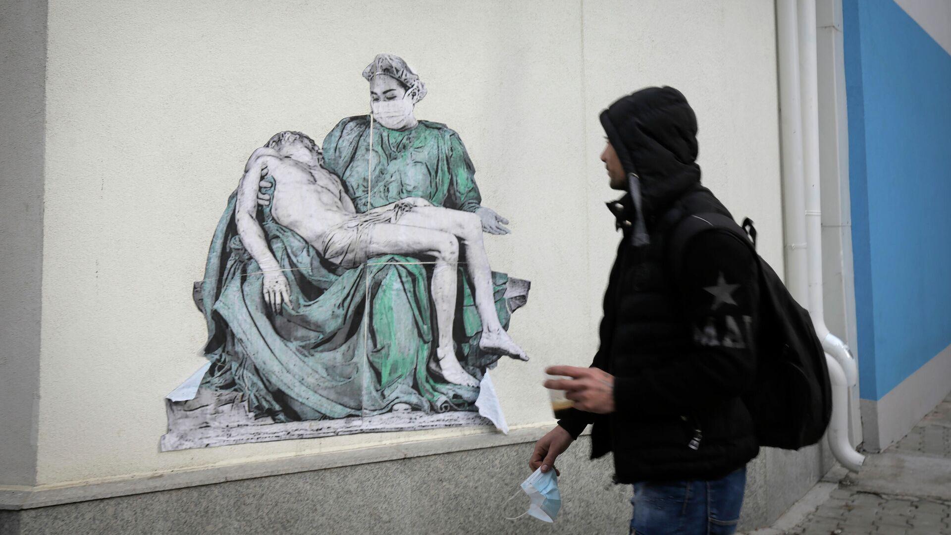 Мужчина проходит мимо копии Пьеты Микеланджело, нарисованной на стене больницы Пирогова в Софии, Болгария - РИА Новости, 1920, 29.07.2021