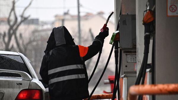 Заправщик заправляет автомобиль на одной из АЗС в Москве