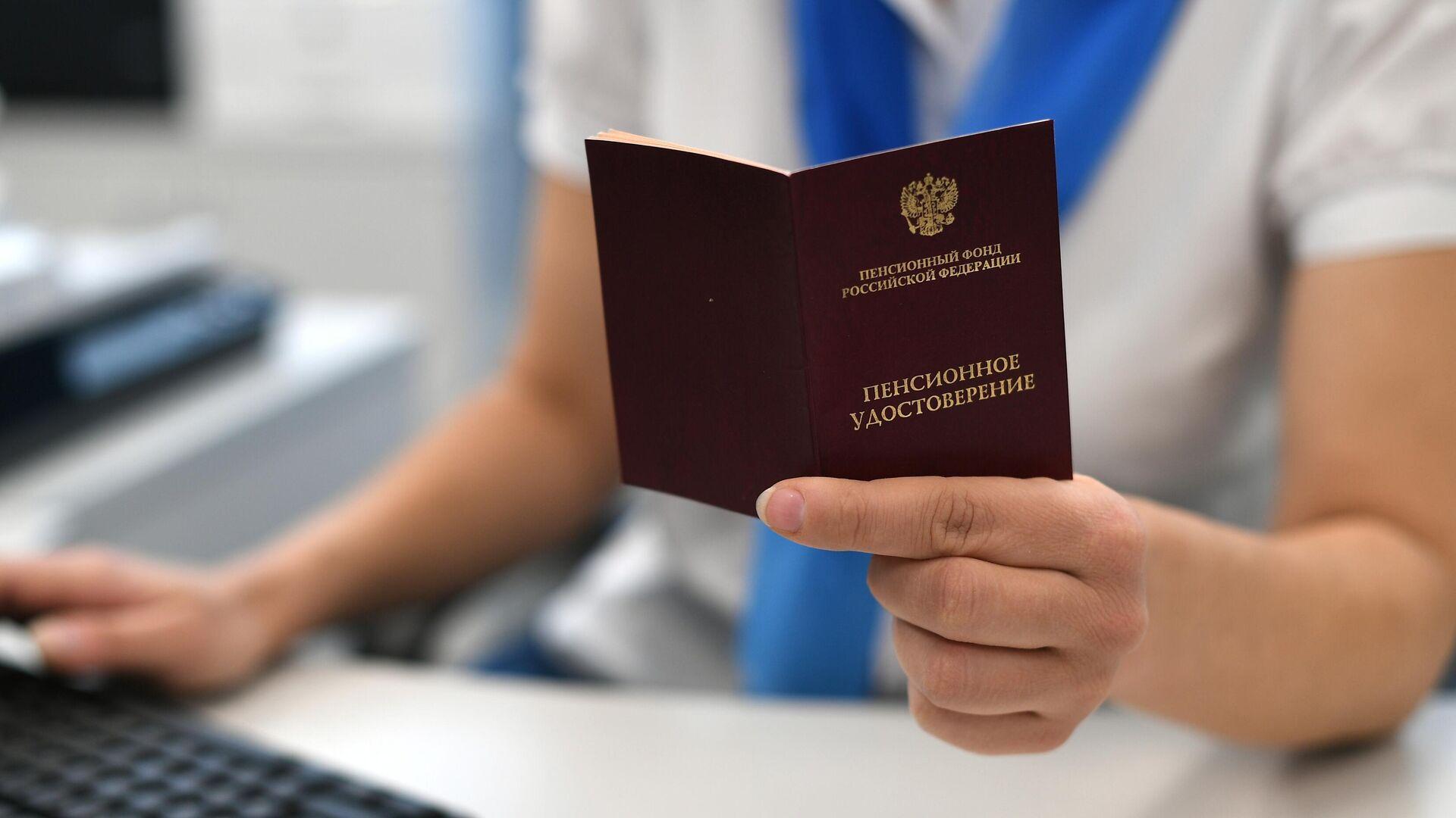 Сотрудник пенсионного фонда держит в руках пенсионное удостоверение - РИА Новости, 1920, 03.08.2021