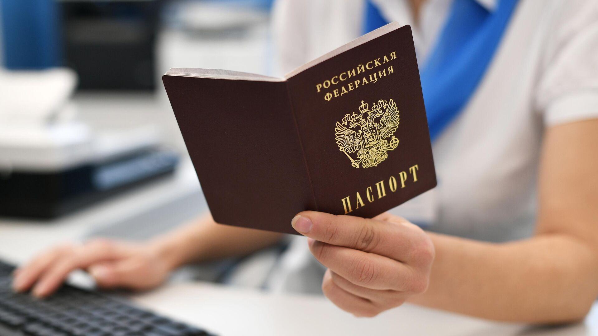 Сотрудник пенсионного фонда держит в руках паспорт РФ - РИА Новости, 1920, 14.10.2021