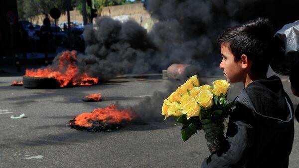 Сирийский мальчик продает цветы на улице во время протестов в Бейруте, Ливан