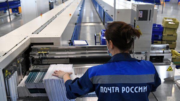 Сотрудница на линии сортировки писем в логистическом почтовом центре Почты России в Новосибирской области