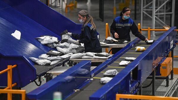 Сотрудницы на линии сортировки мелких посылок и пакетов в логистическом почтовом центре Почты России в Новосибирской области