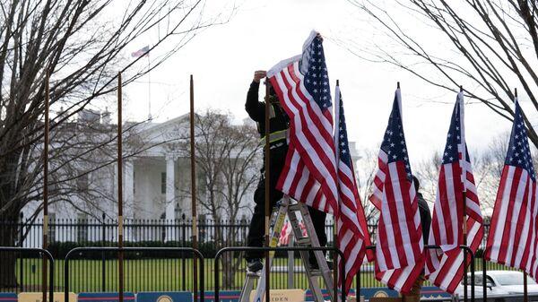 Рабочий устанавливает флаги возле Белого дома в Вашингтоне