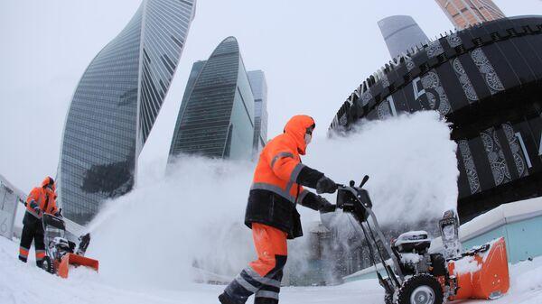 Сотрудники коммунальной службы убирают снег с площади у делового центра Москва-сити