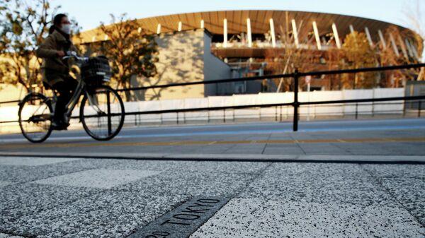 Женщина проезжает мимо Национального стадиона в Токио