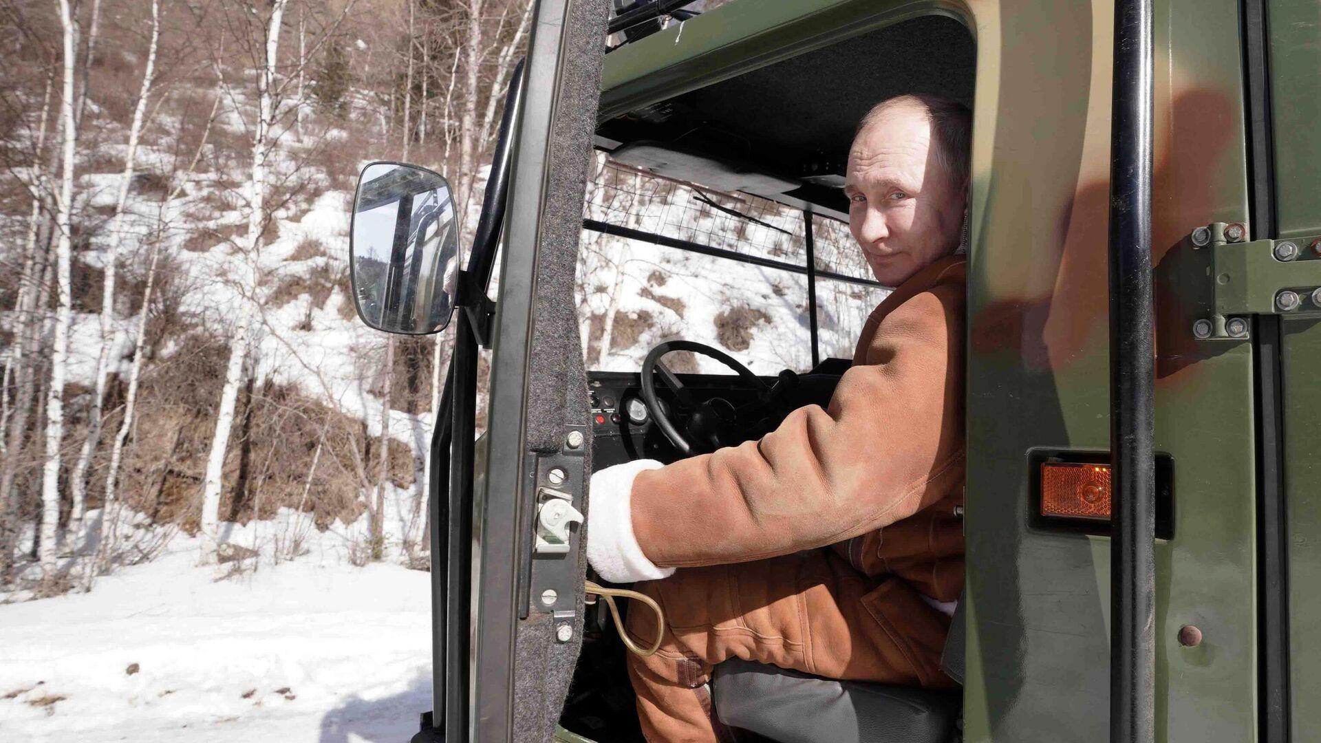 Президент РФ Владимир Путин управляет вездеходом во время прогулки в тайге - РИА Новости, 1920, 22.03.2021