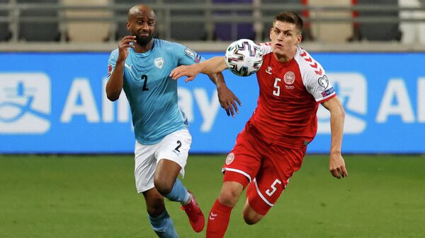Denmark's defender Joakim Maehle (R) vies for the ball with Israel's defender Eli Dasa during the 2022 FIFA World Cup qualifier group F football match between Israel and Denmark at Bloomfield stadium in the Israeli Mediterranean coastal city of Tel Aviv on March 25, 2021. (Photo by JACK GUEZ / AFP)