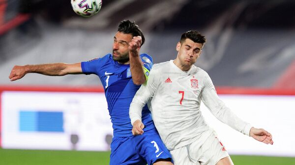 Spain's forward Alvaro Morata (R) challenges Greece's defender Georgios Tzavelas during the FIFA World Cup Qatar 2022 qualification football match between Spain and Greece on March 25, 2021 at Los Carmenes stadium in Granada. (Photo by JORGE GUERRERO / AFP)