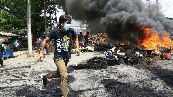 Участники акции протеста против военного переворота сжигают баррикады в Янгоне, Мьянма