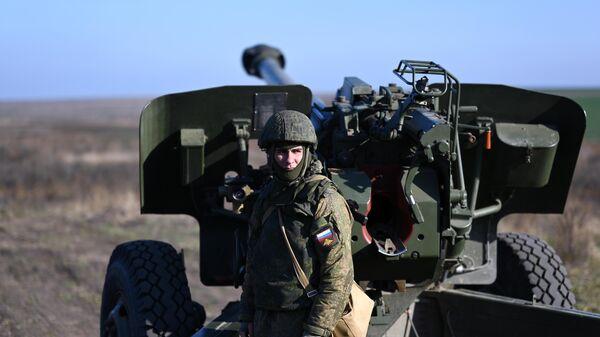 Военнослужащий подготавливает гаубицу к боевым стрельбам