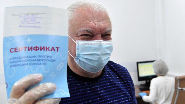 Пожилой мужчина демонстрирует сертификат о вакцинации против новой короновирусной инфекции (COVID-19), полученный после прививки в центре госуслуг Мои документы