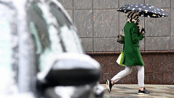 Девушка идет под зонтом во время снегопада в Москве