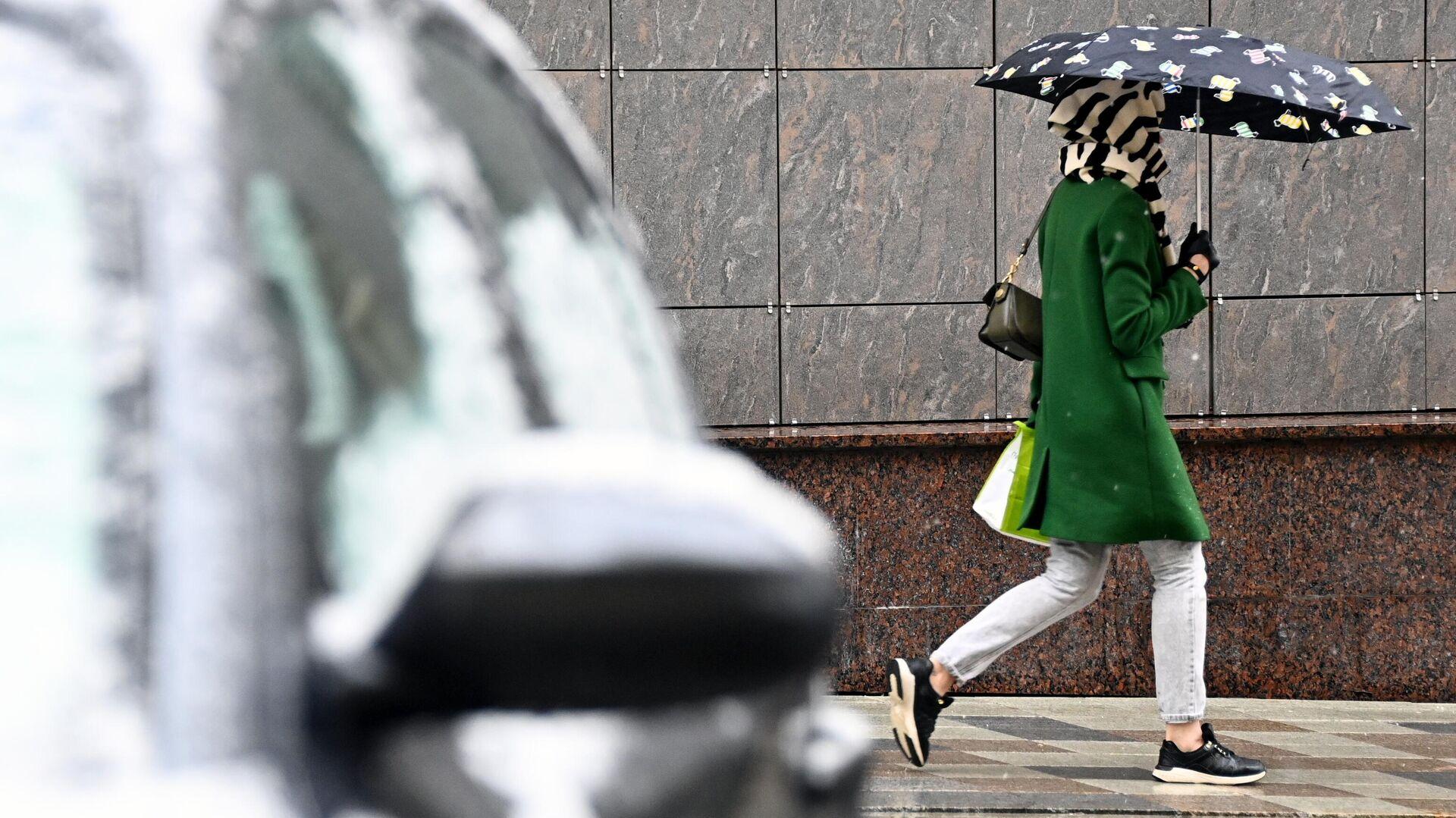 Девушка идет под зонтом во время снегопада в Москве - РИА Новости, 1920, 14.10.2021