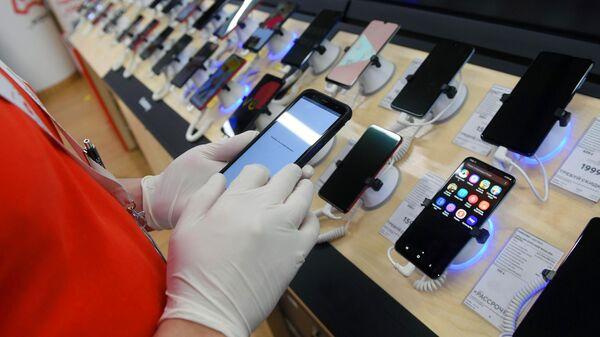 Сотрудник магазина М-видео держит в руках смартфон