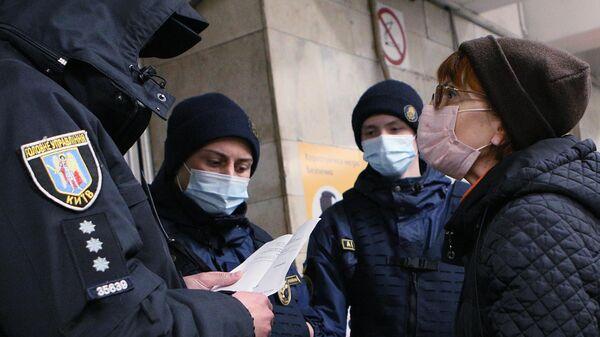 Сотрудники полиции проверяют наличие у женщины спецпропуска для проезда на общественном транспорте на одной из станций метро в Киеве