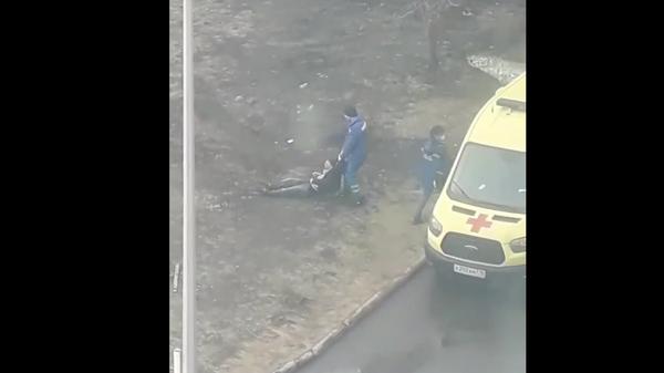 Кадр из опубликованного в соцсетях видео, на котором работник скорой помощи тащит за шиворот нетрезвого мужчину