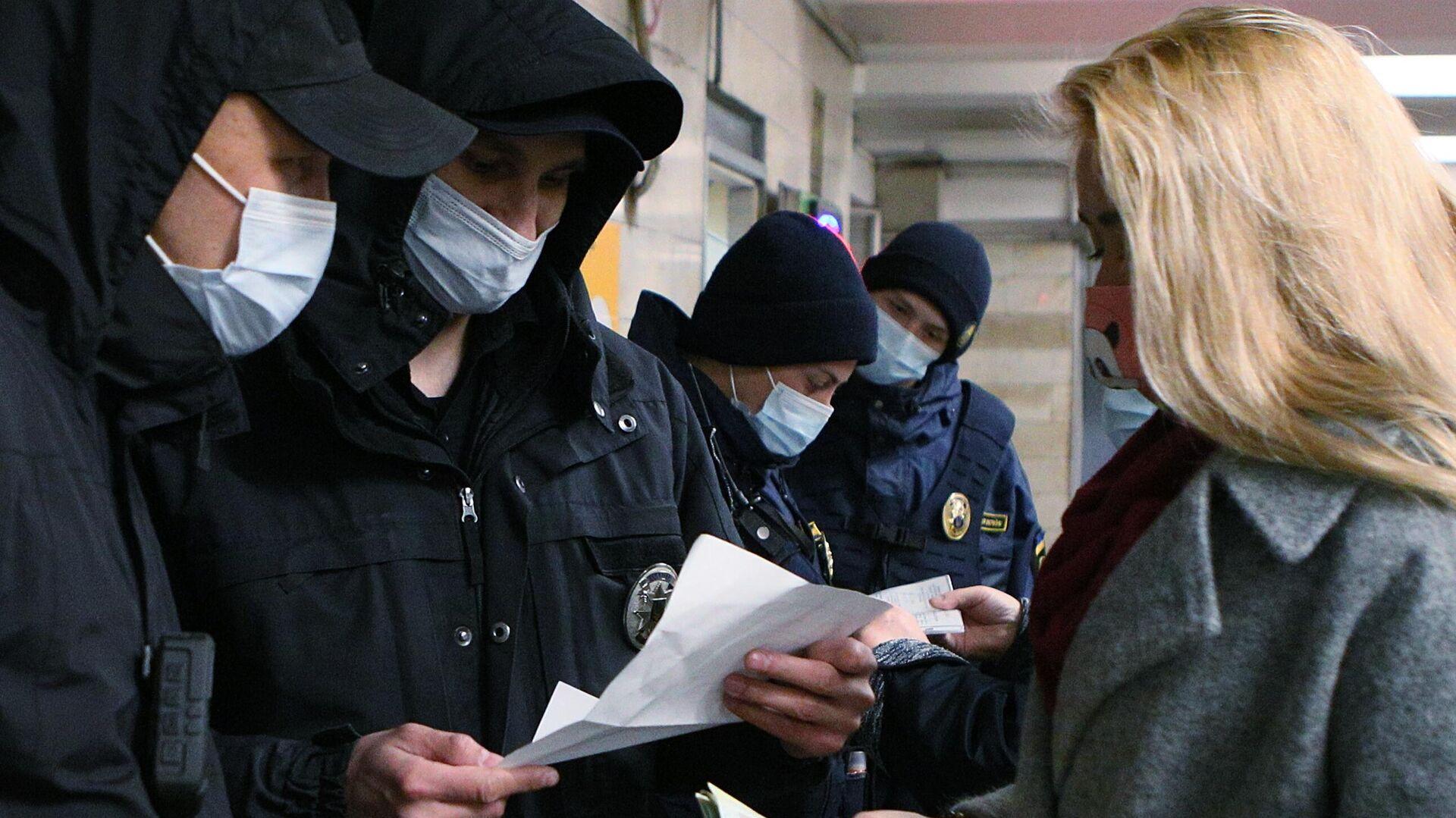 Сотрудники полиции проверяют наличие у девушки спецпропуска для проезда на общественном транспорте на одной из станций метро в Киев - РИА Новости, 1920, 11.10.2021