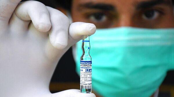 Медицинский работник держит в руках ампулу с российским препаратом от коронавирусной инфекции Гам-Ковид-Вак (Спутник V)