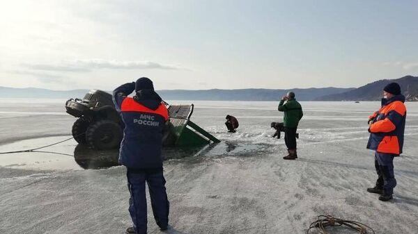 Сотрудники МЧС РФ вытаскивают из воды грузовой автомобиль, который провалился под лед на озере Байкал