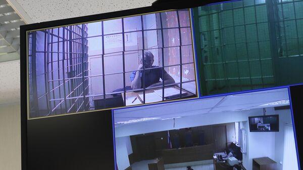 Экс-губернатор Пензенской области Иван Белозерцев на экране монитора в Мосгорсуде