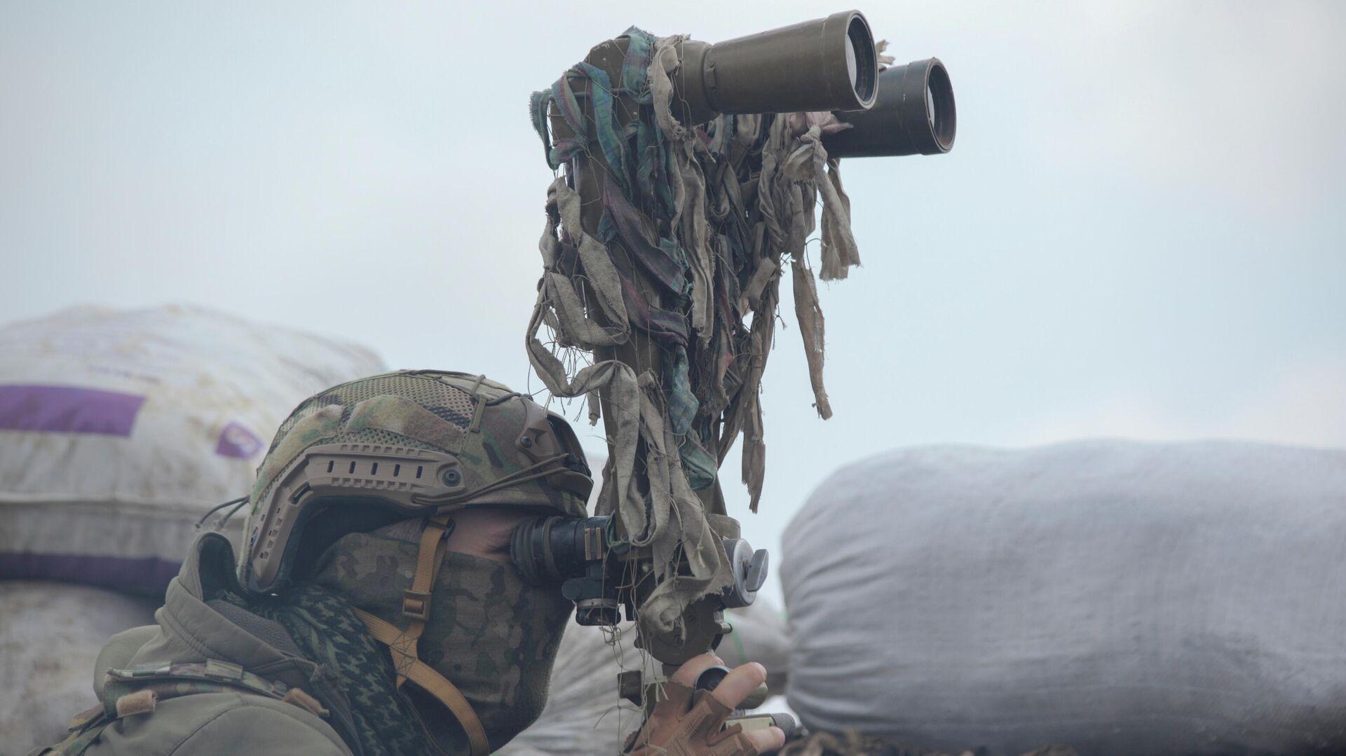 Военнослужащий украинских вооруженных сил осматривает в бинокль территорию на боевых позициях на линии разделения близ города Донецк - РИА Новости, 1920, 14.04.2021