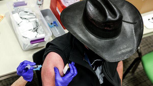 Пациент получает дозу вакцины Johnson & Johnson COVID-19,  одобренной FDA США