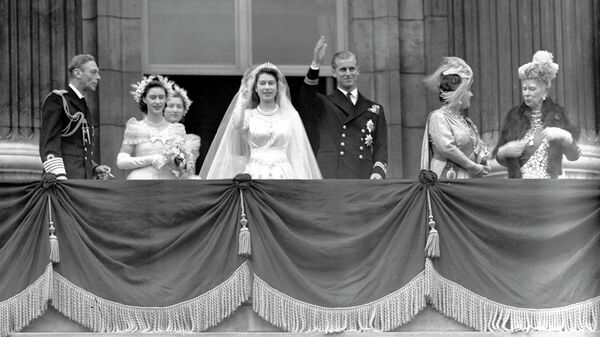 Королева Великобритании Елизавета II и ее супруг герцог Эдинбургский машут толпе с балкона Букингемского дворца