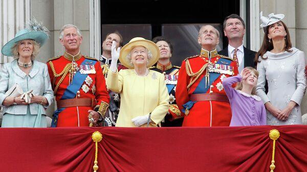 Королева Великобритании Елизавета II и ее семья смотрят за пролетом самолета Королевских ВВС с балкона Букингемского дворца