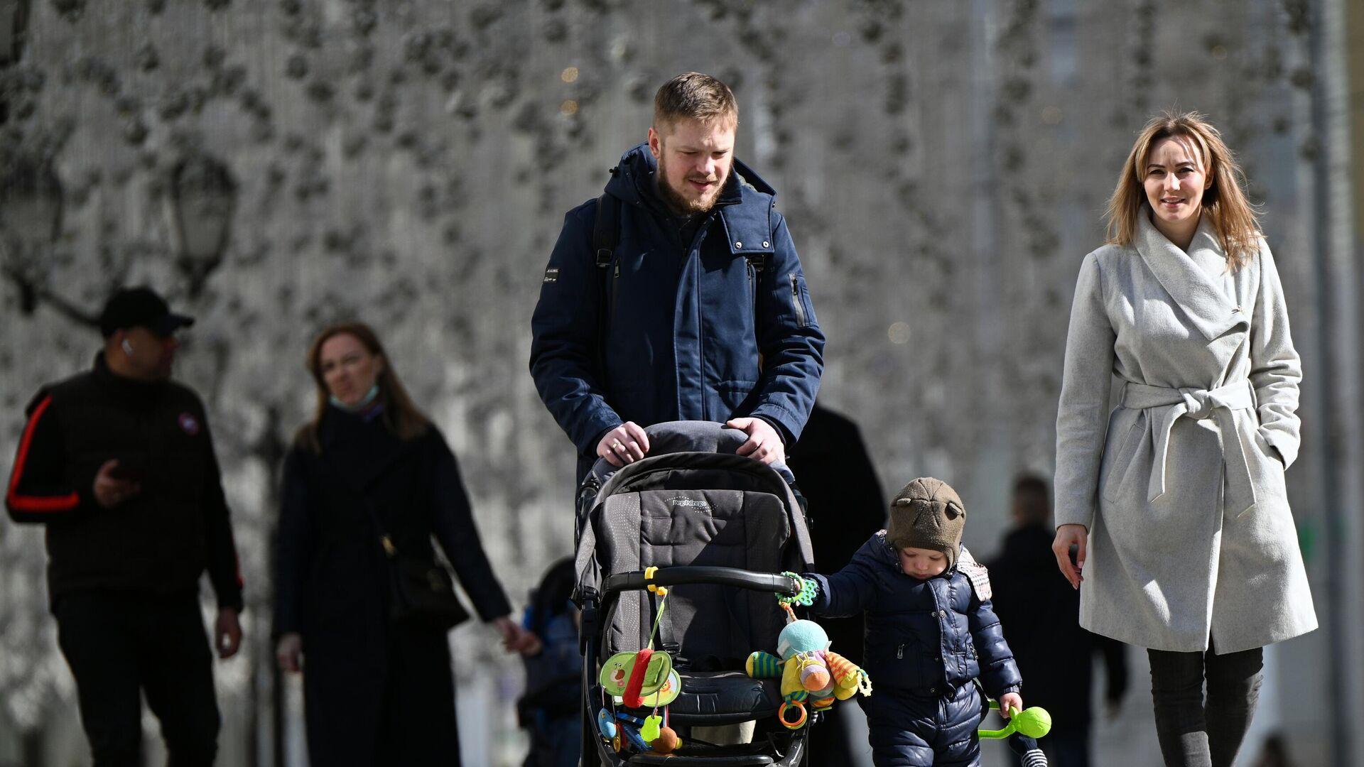 Молодые люди с ребёнком во время прогулки на улице Никольская в Москве - РИА Новости, 1920, 21.04.2021