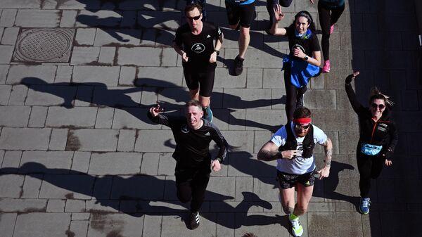 Молодые люди во время пробежки на Пречистенской набережной в Москве