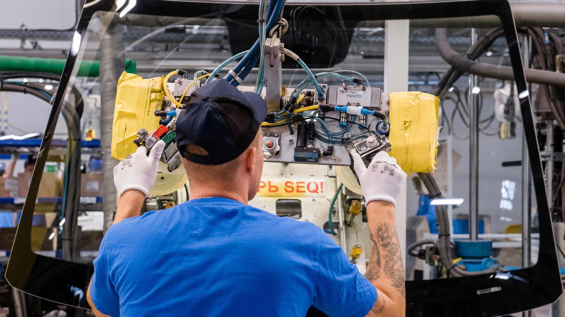 Рабочий устанавливают стекла в автомобиль на участке сборочного конвейера завода Hyundai Motor Manufacturing Rus в Санкт-Петербурге - РИА Новости, 1920, 29.04.2021