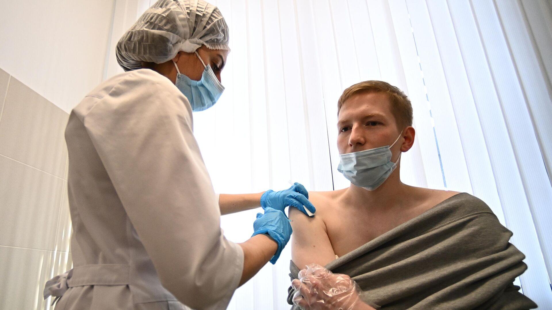 Мужчина во время вакцинации от COVID-19 в центре госуслуг Мои документы в Москве - РИА Новости, 1920, 14.04.2021