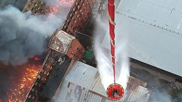 Сброс воды с вертолета Ми-8 Западного военного округа на горящее здание фабрики Невская мануфактура на Октябрьской набережной в Санкт-Петербурге. Кадр видео
