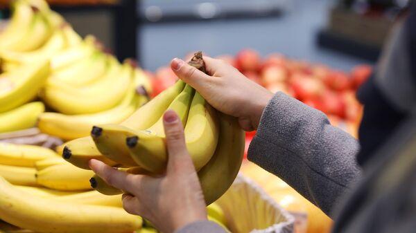 Покупательница выбирает бананы в магазине