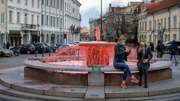 Девушки в защитный масках фотографируются у фонтана, окрашенного в красный цвет, во всемирный день гемофилии в Вильнюсе