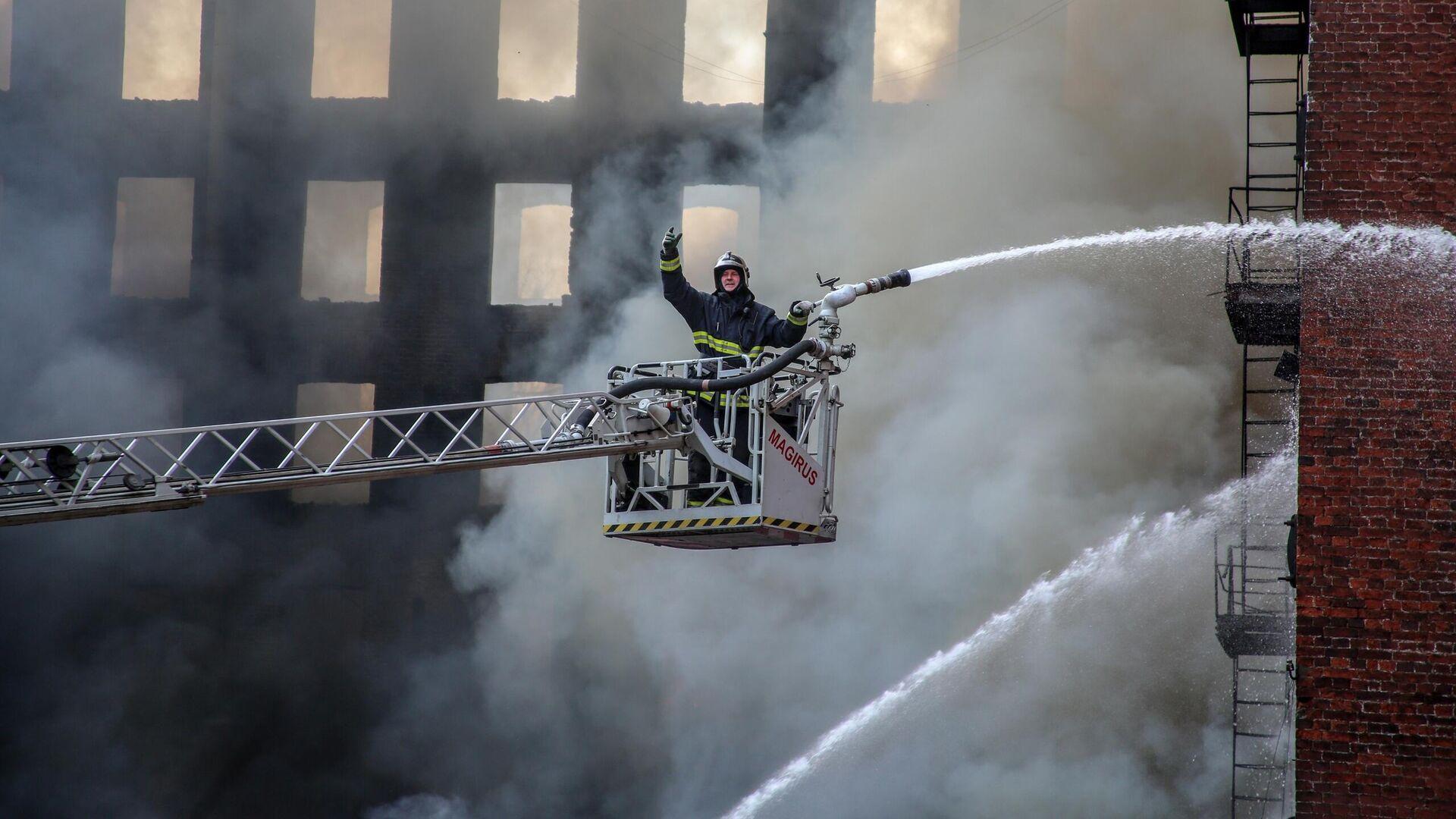Пожарный во время тушения пожара в Невской мануфактуре - РИА Новости, 1920, 30.06.2021