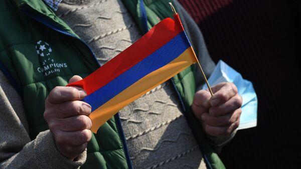 Флажок в руках участника протестного митинга в Армении
