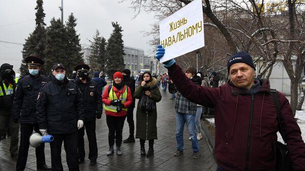Сотрудники полиции и участник несанкционированной акции в поддержку Алексея Навального на площади Ленина в Новосибирске