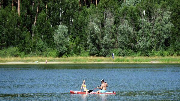 Отдыхающие плавают на лодке по озеру Лебяжье в Казани