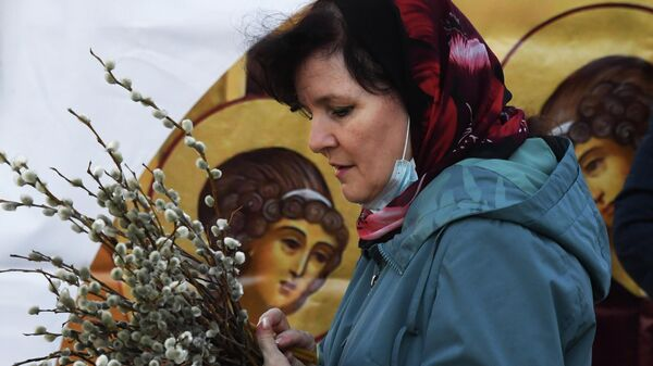 Женщина у Покровского кафедрального собора во Владивостоке во время праздника Входа Господня в Иерусалим. 25 апреля 2021