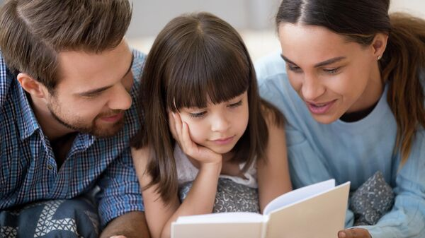Родители с дочерью, читающей книгу