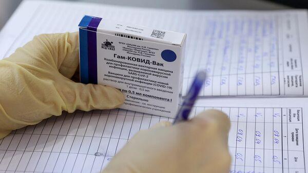 Медицинская сестра держит в руке упаковку с вакциной Гам-КОВИД-Вак (Спутник V) в пункте вакцинации от COVID-19