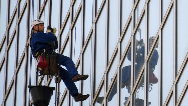 Промышленный альпинист моет фасад высотного здания