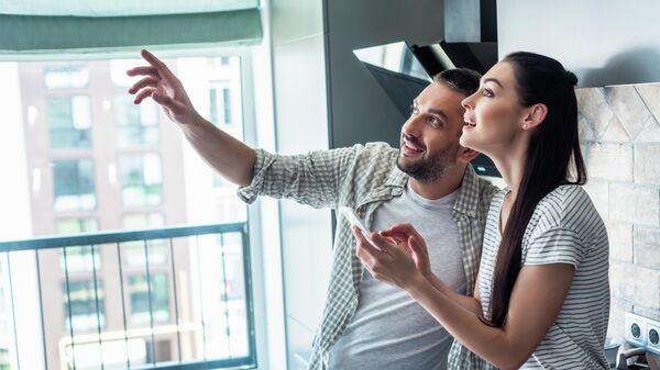 Молодая пара со смартфоном в Умном доме